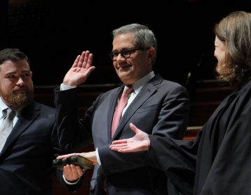 Philadelphia District Attorney Larry Krasner sworn in by his wife, Judge Lisa Millett Rau with son Nathan holding Bible.
