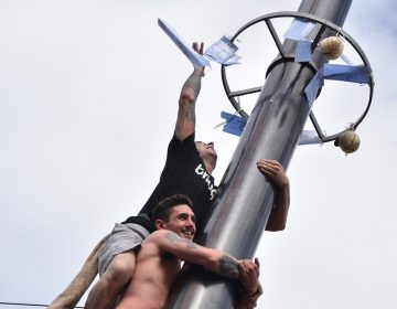 Competitors in the greased pole challenge at the Italian Market Festival reach the prizes at the top.