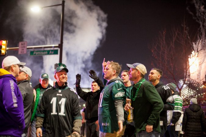 Eagles fans taunt a Vikings fan in South Philadelphia following their win over the Minnesota Vikings in the NFC Championship Game Sunday Night. (Brad Larrison for WHYY)