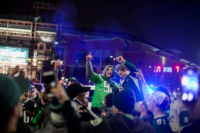Eagles Fans celebrate near Xfinity Live after their win over the Minnesota Vikings in the NFC Championship Game Sunday. (Brad Larrison for WHYY)