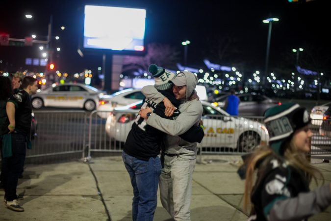 Eagles fans hug outside of Xfinity Live after an Eagles touchdown in the NFC Championship Game against the Minnesota Viking Sunday Night. (Brad Larrison for WHYY)