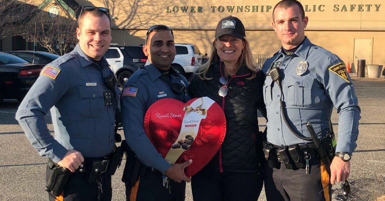 The dog's owner presents a gift to the three Lower Township Police officers that responded to the lake last Sunday.