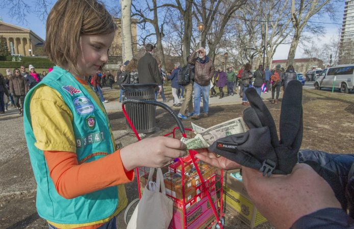 Adah Di'Alba sells Girl Scout Cookies at the base of the Art Museum. Di'Alba was attending the march with her mother Ginna Di'Alba, and grandmother Andrea Cauble, both former Girl Scouts. (Jonathan Wilson for WHYY)