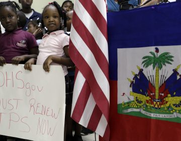 Children hold signs at a November news conference in Miami in support of renewing temporary protected status for immigrants from Central America and Haiti. (Lynne Sladky/AP)