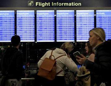 Travelers walk and check their flight information in Terminal 3 at Chicago's O'Hare International Airportin December