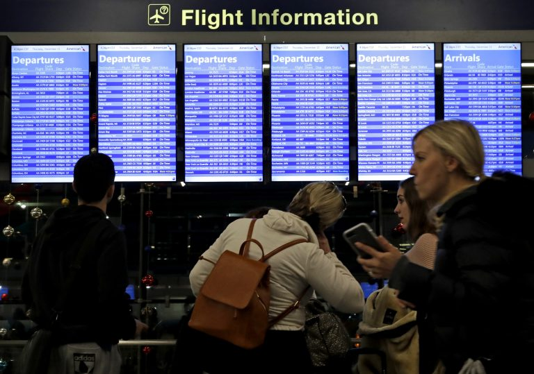 Travelers walk and check their flight information in Terminal 3 at Chicago's O'Hare International Airport in December