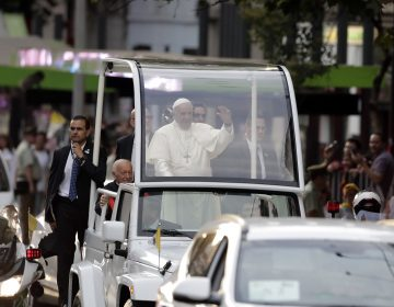 Pope Francis waves at followers on his way to the Apostolic Nunciature in Santiago, Chile, on Monday.