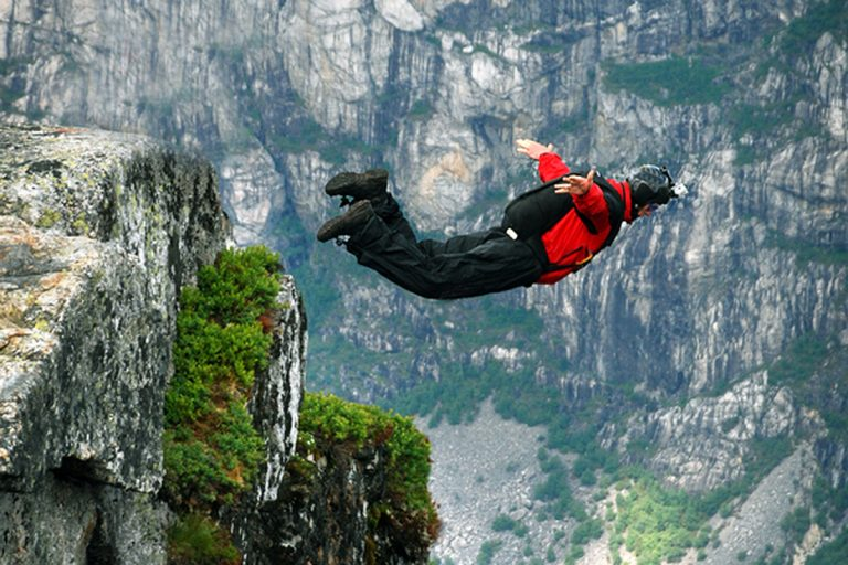 Man jumping off a cliff with a parachute