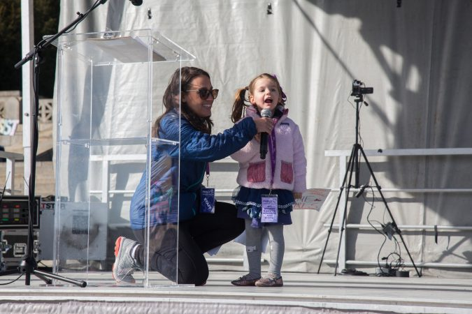 Laura Arblaster helps her 3 year old daughter, Elizabeth Zangrilli, raise her voice at the 2018 Women's March on Philadelphia, January 20, 2018. (Emily Cohen for WHYY)