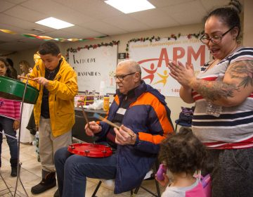 Asaf Barrios, 11, jams out on his steele drum accompanied by his father, Raul, at APM's Three Kings Day/Octavious celebration for displaced families from Puerto Rico in North Philadelphia on January 12 2018. (Emily Cohen for WHYY)