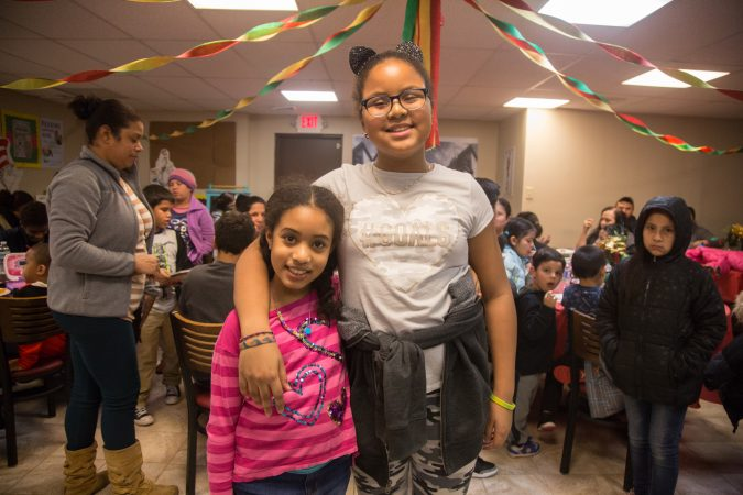 Sisters Layla, 8, (left) and Lia, 11, pose for a photo at APM's Three Kings Day/Octavious celebration for diplaced families from Puerto Rico in North Philadelphia on January 12 2018. (Emily Cohen for WHYY)