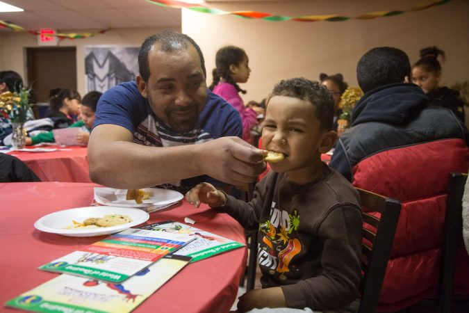 Nelson D'Jesus playfully feeds his son, Mikeli,4, a sweet at APM's Three Kings Day/Octavious celebration for diplaced families from Puerto Rico in North Philadelphia on January 12 2018. (Emily Cohen for WHYY)