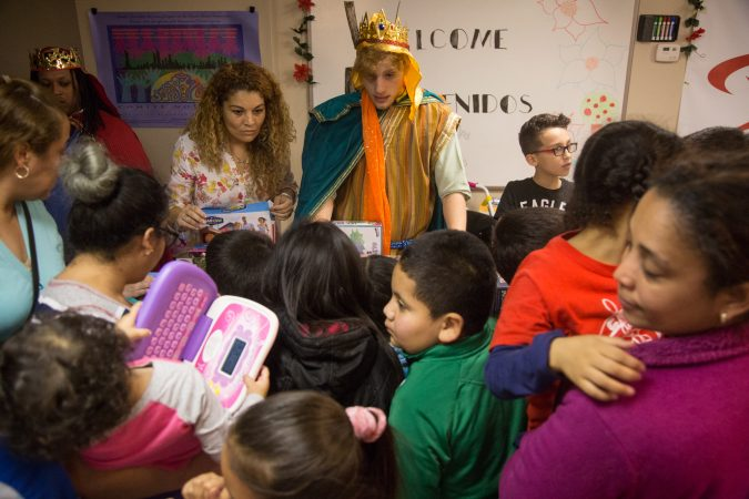 Tom Diagostino passes out gifts as one of the three kings to the children at the celebration. APM threw a Three Kings Day/Octavious celebration for diplaced families from Puerto Rico in North Philadelphia on January 12 2018. (Emily Cohen for WHYY)