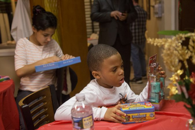 Children take a closer look at their new toys at APM's Three Kings Day/Octavious celebration for diplaced families from Puerto Rico in North Philadelphia on January 12 2018. (Emily Cohen for WHYY)
