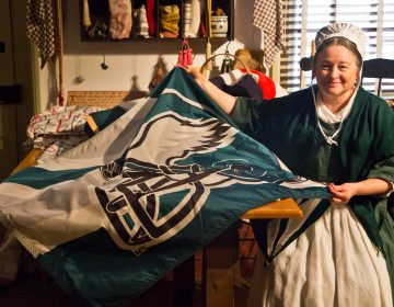 A Betsy Ross reenactor sews an Eagles flag the Monday before the Philadelphia football team heads to the Super Bowl.