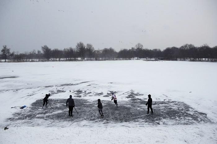 Youths play ice hockey on a frozen pond at Philadelphia's Franklin Delano Roosevelt Park during a winter storm, Thursday, Jan. 4, 2018. (AP Photo/Matt Slocum)