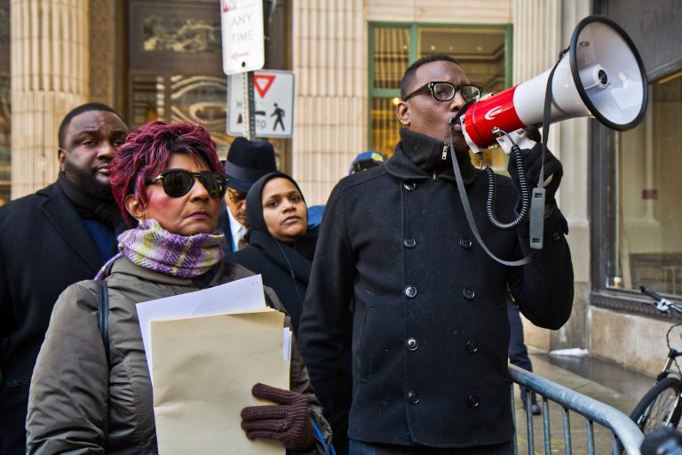 Christine Riddick, mother of Eric Riddick, (left) his wife Dana Baker-Riddick, (center) and Black Lives Matter activist Asa Khalif protest outside the Philadelphia district attorney's office in an attempt to deliver information they say will prove the innocence of Eric Riddick, who's been incarcerated for 26 years. (Kimberly Paynter/WHYY)
