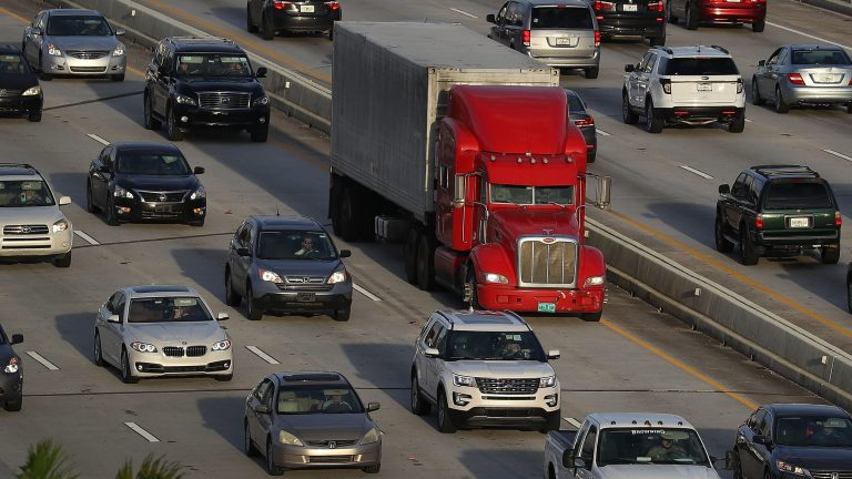 A tractor-trailer rolls along the highway in Miami last November. The trucking industry needs to hire almost 900,000 more drivers in order to meet rising demand, according to an industry analysis. (Joe Raedle/Getty Images)