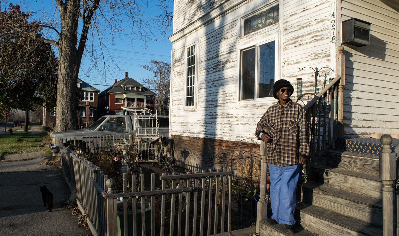 Gloria Duncans-Kidd stands on the porch of her Detroit home.