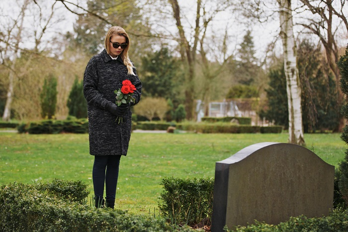 Young woman visiting a loved one at the cemetery paying respects with fresh rose flowers. Female grieving at graveyard.