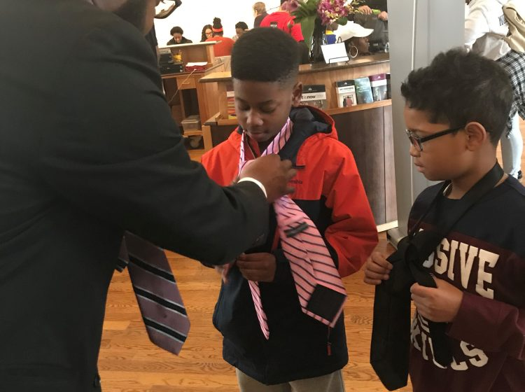William Merritt Jr. teaches boys how to fix a tie during MLK Day of Service event. (Nichelle Polston/WHYY)