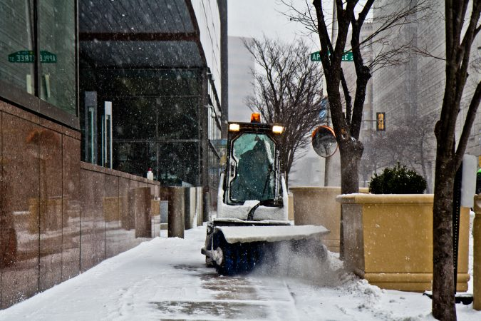 A Bobcat driver with a front brush works to keep the sidewalks around the Federal Reserve clear. (Kimberly Paynter/WHYY)