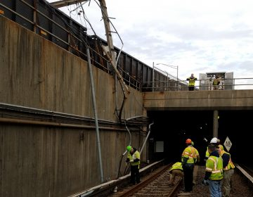Workers assessing damage from a Conrail train's collision with a PATCO power pole.