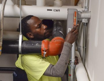 Richard Tumushime, an electrician with Pittsburgh-based Energy Independent Solutions, works with a crew to put the finishing touches on wiring a solar panel system at the new Forest Hills Municipal Building. (Amy Sisk/StateImpact Pennsylvania)