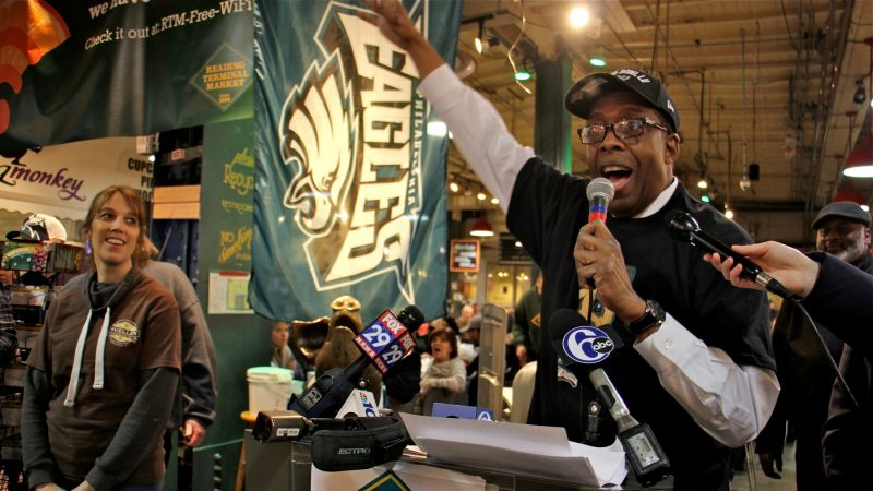 City Council President Darrell Clarke sings the Eagles fight song at Reading Terminal Market after announcing a bet with his Boston counterpart, Andrea Campbell, over the outcome of the Super Bowl. (Emma Lee/WHYY)
