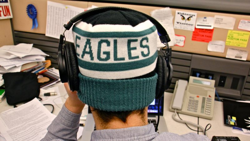 WHYY education reporter Avi Wolfman-Arent works in his Eagles hat. (Emma Lee/WHYY)