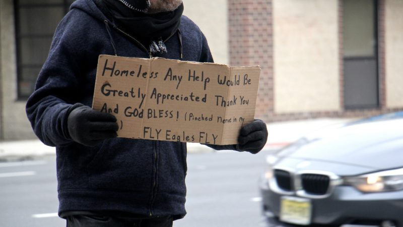 A homeless includes a plug for the Eagles on his sign as he works the corner of 5th and Callowhill streets . (Emma Lee/WHYY)