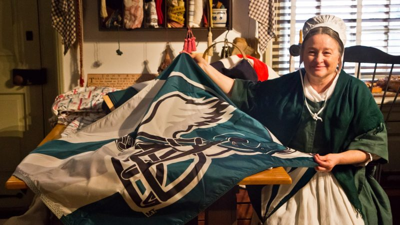 A Betsy Ross re-enactor sews an Eagles flag the Monday before the Philadelphia football team heads to the Super Bowl. (Kimberly Paynter/WHYY)