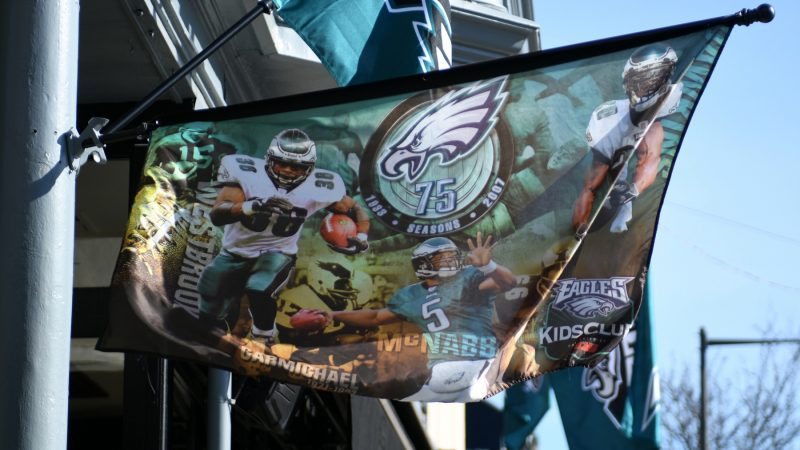 Flags in support of the Philadelphia Eagles hang above a bar in Manayunk on Wednesday. The banner harkens back to the Eagles 75th anniversary season in 2007, when the team compiled an 8–8 record and a last-place finish in the NFC East. (Bastiaan Slabbers for WHYY)