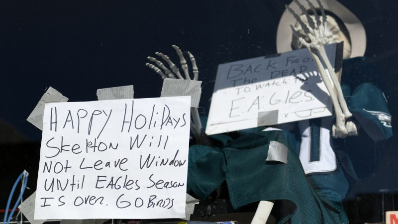 A skeleton in an Eagles jersey sits in the window of a store in Manayunk. (Bastiaan Slabbers for WHYY)