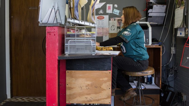 Colleen McClure, 41, completes some front office work while showing off her Eagles pride at Girls Auto Shop in Upper Darby. (Emily Cohen for WHYY)