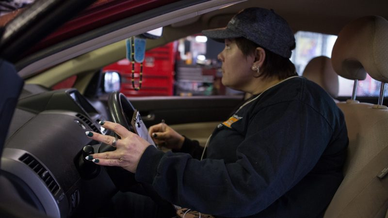 Sue Sweeney, 41, the shop forewoman for Girls Auto Shop, shows off her Eagles manicure as she checks lights on a car that has come into the shop. (Emily Cohen for WHYY)
