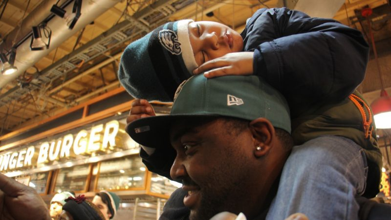 Young Eagles fan Howard McKelvey IV falls asleep on his father's shoulders during an Eagles event at Reading Terminal Market. (Emma Lee/WHYY)
