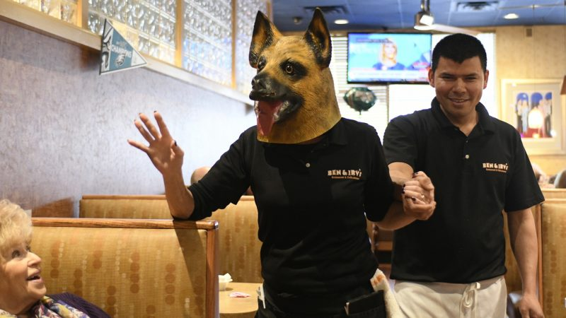 "In an ""underdog"" mask, Kathy Ryder greets patrons at Ben & Irvs Restaurant in Huntingdon Valley, Pennsylvania, on Thursday. (Bastiaan Slabbers for WHYY)"