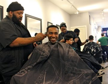 Mike Jordan (left) and Mark Belle chat at South Street Barbers. (Emma Lee/WHYY)