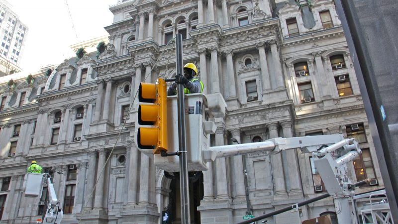Workers replace the traffic lights on Market Street east of City Hall after celebrating Eagles fans tore them down. (Emma Lee/WHYY)