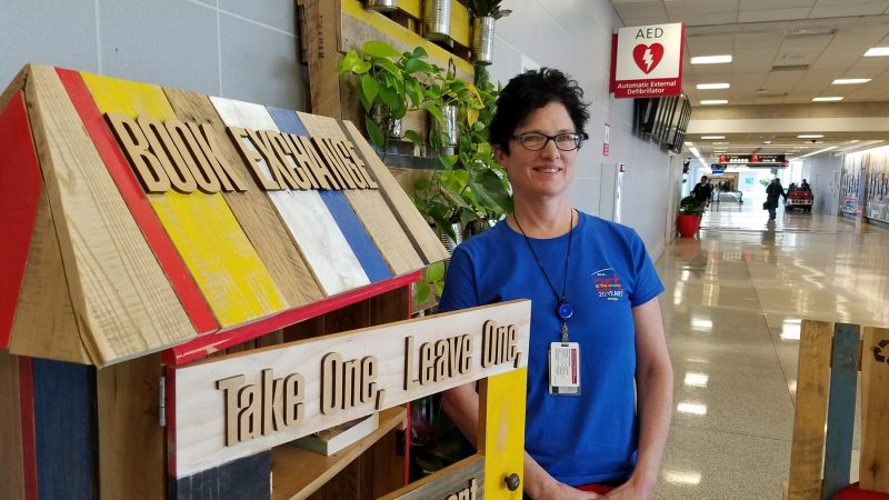 Leah Douglas, curator at the Philadelphia International Airport, stocks the book trade she designed with books left behind in airplanes. (Peter Crimmins/WHYY)