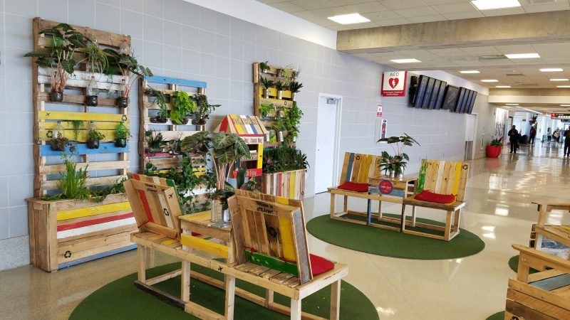 A seating area/book trade designed by Leah Douglas is made from leftover pallets. The book trade is stocked with books left behind in airplanes. (Peter Crimmins/WHYY)