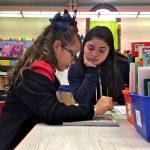 High School senior Shalia Alejandro (center) helps Soriely Quinonez, a student at Cramp Elementary School.