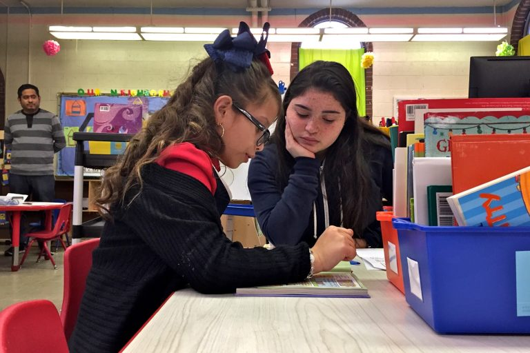 High School senior Shalia Alejandro (center) helps Soriely Quinonez, a student at Cramp Elementary School.