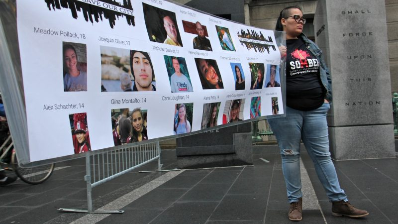 Carmen Pagan of SOMBER (Sisters of Murdered Brothers Emerging and Revolutionizing), whose brother, Richard Davila was murdered two years ago, helps to hold a banner identifying the 17 people killed in the Parkland, Florida, school shooting. (Emma Lee/WHYY)