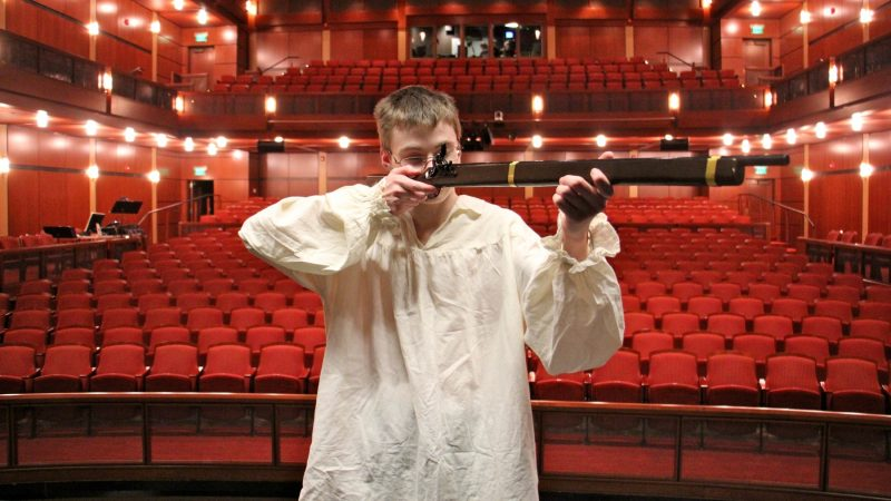 Penn Charter student Etthan Willis raises a prop gun on stage at the David L. Kurtz Center for the Performing Arts before a performance of