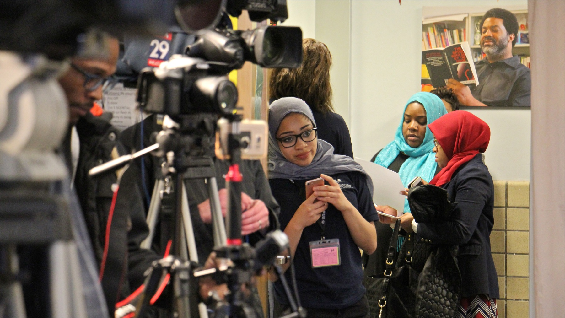 Nasihah Thompson-King, a Mastery Shoemaker Charter School basketball player who was benched because she had not obtained a waiver to wear her hijab, looks into a room full of media representatives before a press conference at her school.