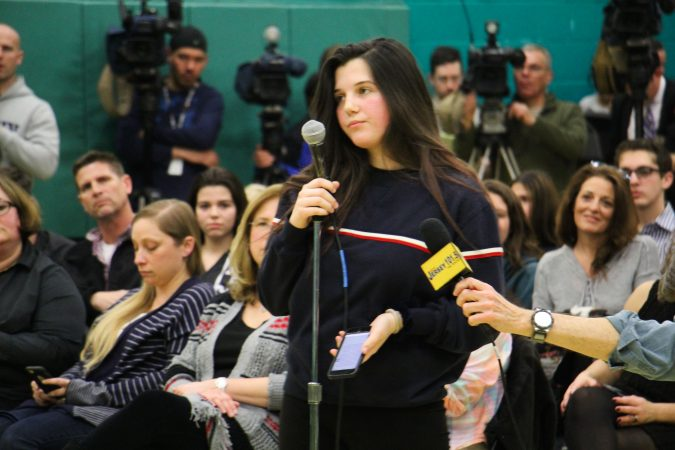 Cherry Hill East senior Julianna Martinez is the first to speak at a school board meeting where hundreds turned out to discuss school security and the rumored suspension of a teacher for his remarks to students about the Parkland school shooting. (Emma Lee/WHYY)