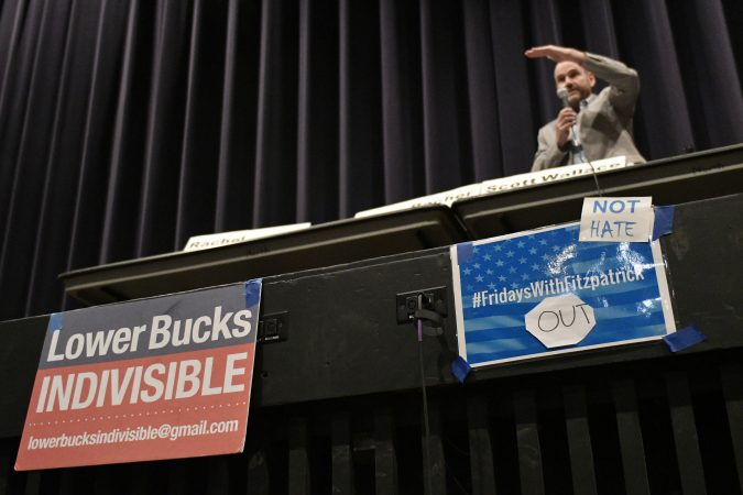 Signs mounted on the edge of the stage during a candidate forum with Democratic candidates for the newly-drawn 1st Congressional District at a candidate forum in Newtown, Pa. on Tuesday evening. (Bastiaan Slabbers/for WHYY)