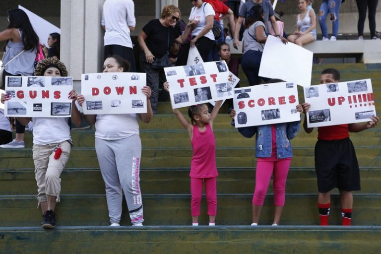 """A group holds signs reading, """"Guns Down Test Scores Up"""" during a protest in Fort Lauderdale, Florida. (AP Photo/Brynn Anderson)"""